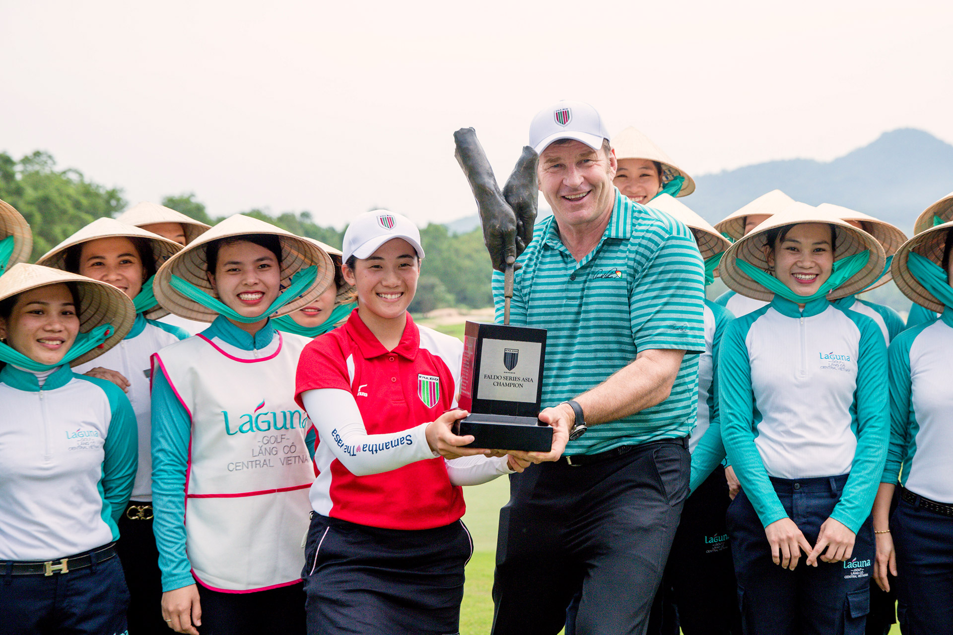 Suzuka Yamaguchi poses with Sir Nick Faldo and Laguna Lăng Cô caddies after her historic victory